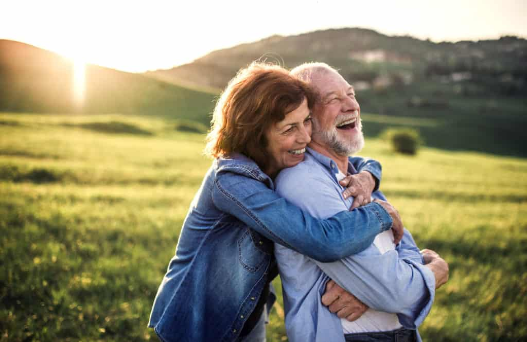 Side-view-of-senior-couple-hugging-outside-in-spring-nature-at-sunset.-1027141710_5568x3616-1024x665-1